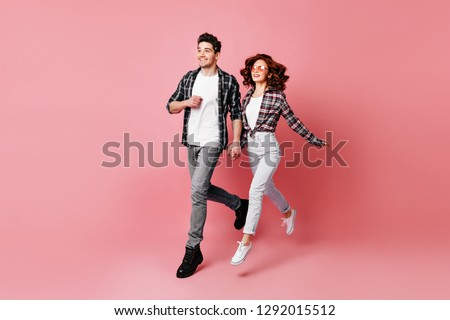 Full length shot of caucasian couple isolated on pink. Man in casual attire chilling with girlfriend.