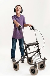 Full length shot of disabled boy with cerebral palsy in headphones listening to music, taking steps with his walker isolated over white background. Children with disabilities and special needs