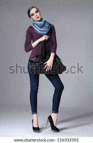 full length shot of fashion model in scarf posing on grey background