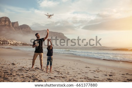 Full length shot of father and son operating the drone by remote control at the sea shore. Young man and little boy flying drone at the sea shore, having fun during summer vacation.