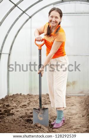 full length shot of female gardener with spade in greenhouse