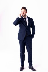 Full length shot of handsome businessman wearing suit and talking with somebody on his mobile phone while standing at isolated white background.