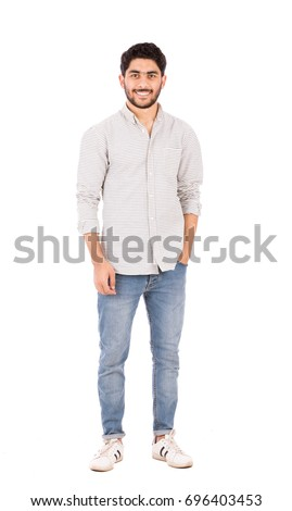 Full length shot of handsome happy beard young man smiling and standing confidently, guy wearing gray shirt and jeans, isolated on white background