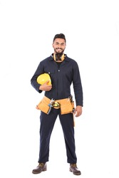 Full length shot of happy beard worker smiling and holding a yellow helmet, guy wearing dark blue workwear and belt equipment, isolated on white background