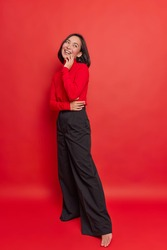 Full length shot of happy dreamy brunette young Asian woman has positive expression wears turtleneck black loose trousers stands against vivid red background thinks about something very pleasant