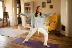 Full length shot of happy energetic mature woman in casual clothes exercising at home because of social distancing, practicing yoga on mat, standing in warrior ii pose. Age, wellness and health