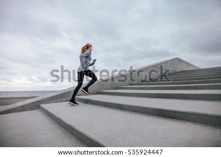 Full length shot of healthy woman climbing up on stairs. Fitness female exercising outdoors in morning.