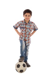 Full-length shot of little boy standing hands on waist putting his foot on the football on the ground, isolated on a white background.