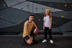 Full length shot of male instructor and active little girl looking at camera, standing against artificial training climbing wall. Concept of sport life and rock climbing. Selective focus on people