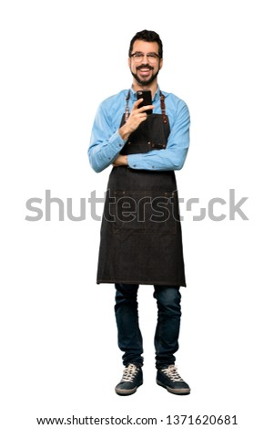 Full-length shot of Man with apron sending a message with the mobile over isolated white background Foto stock ©