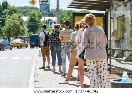 Full length shot of people wearing masks waiting, standing in line, keeping social distance at bus stop. Coronavirus, pandemic concept. Selective focus on guy in the queue. Horizontal shot Сток-фото ©