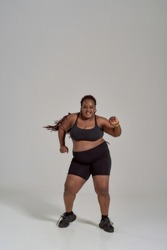 Full length shot of plump, plus size african american woman in sportswear having fun, dancing in studio over grey background. Concept of body positive. Vertical shot