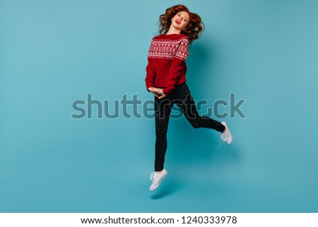 Full-length shot of slim adorable girl in new year sweater. Ginger young woman jumping on blue background.