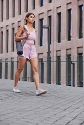 Full length shot of sporty woman in activewear walks in city carries rolled up karemat goes to gym to have fitness training poses against ancient building. People healthy lifestyle and sport