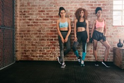 Full length shot of three young female in sportswear standing together in gym. Multiracial women in healthclub looking at camera.