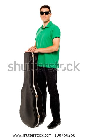 Full length shot of trendy young man posing with guitar case over white