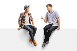 Full length shot of two young men sitting on a panel and talking isolated on white background