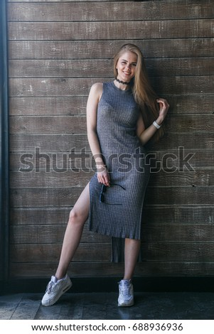 Full length shot of young blonde model in grey dress posing in front of a wooden building #688936936