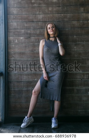 Full length shot of young blonde model in grey dress posing in front of a wooden building #688936978