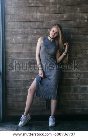 Full length shot of young blonde model in grey dress posing in front of a wooden building #688936987