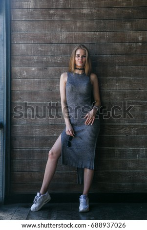 Full length shot of young blonde model in grey dress posing in front of a wooden building #688937026