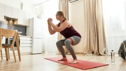 Full length shot of young curvy woman in sportswear exercising using resistance band at home. Determination, will power, sport concept. Horizontal shot