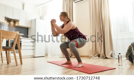 Full length shot of young curvy woman in sportswear exercising using resistance band at home. Determination, will power, sport concept. Horizontal shot Photo stock ©