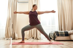 Full length shot of young curvy woman in sportswear practicing yoga on a mat at home. Determination, will power, sport concept. Horizontal shot