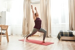 Full-length shot of young curvy woman in sportswear standing in Warriror I pose on a yoga mat at home. Determination, will-power, sport concept. Horizontal shot