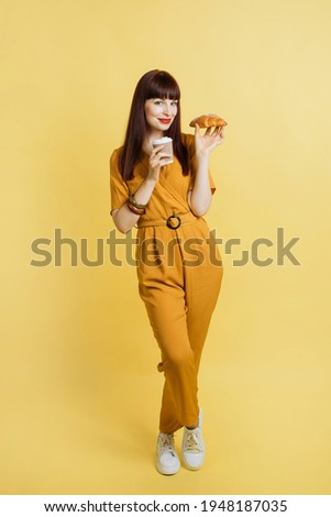 Full-length shot of young lady in elegant trendy ocher overalls and sneakers, posing on yellow background and holds delicious croissant and coffee to go. Food and drink promo ad. Foto stock ©