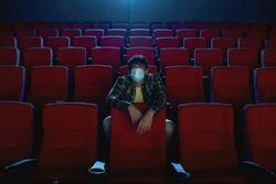 Full length shot of young man in protective face mask watching a movie, visiting cinema alone during coronavirus pandemic. Social distance concept. Front view. Horizontal shot