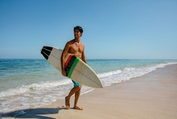 Full length shot of young man with surf board on beach. Handsome caucasian male holding surfboard walking on the sea shore and looking away.