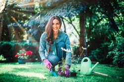 Full length shot of young woman gardening at home in the backyard. Happy woman wearing casual clothes while planting flowers.