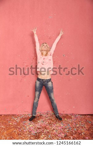 full length shot, one young happy, smiling woman arms outstretched high in air with confetti falling down on floor, 20-29 years old, long blond hair. Shot in studio on pink background.
