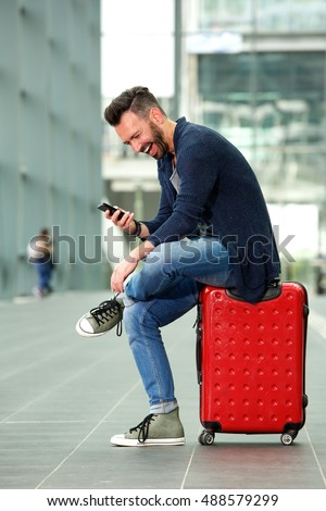Full length side portrait of cheerful man sitting on suitcase and using cell phone at train station #488579299