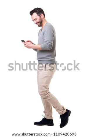 Full length side portrait of man walking with mobile phone #1109420693