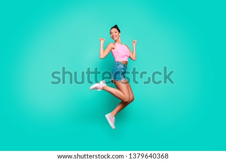 Full length side profile body size photo beautiful she her funny stylish trendy hairdo jump high lucky lottery wear casual pink tank-top jeans denim shorts isolated teal turquoise background