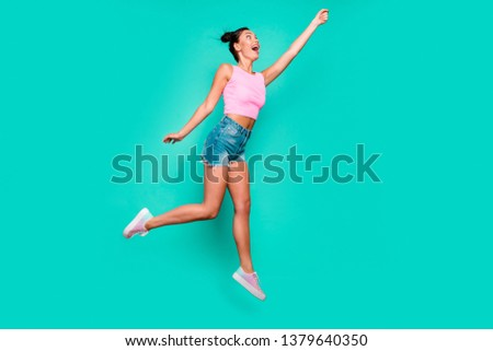 Full length side profile body size photo beautiful she her jump high trendy stylish hairdo pretend umbrella flight wear casual pink tank-top jeans denim shorts isolated teal turquoise background