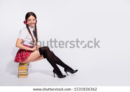 Full length side profile body size photo beautiful she her teacher sit book pile diligent student tails flirty dress check pantyhose wear specs short red checkered costume isolated white background