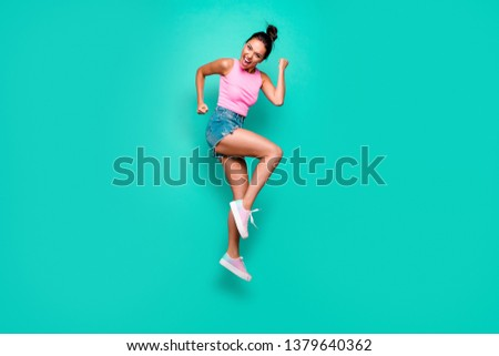 Full length side profile body size photo beautiful she her trendy hairdo jump high yell scream shout yeah wild roar wear casual pink tank-top jeans denim shorts isolated teal turquoise background