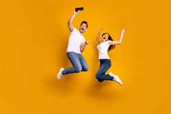 Full length side profile body size photo funky funny two people she her he him his guy lady jump high show v-sign make take selfies wear casual jeans denim white t-shirts isolated yellow background