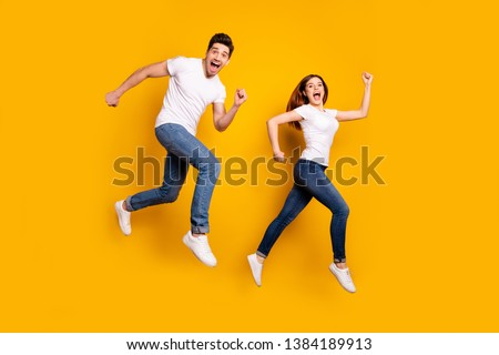 Full length side profile body size photo funky she her he him his pair jumping high hurry shopping raised fists yell scream shout loud wear casual jeans denim white t-shirts isolated yellow background #1384189913