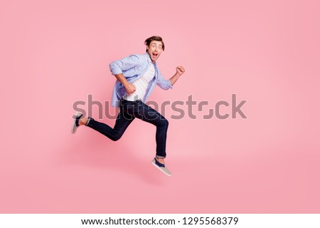 Full length side profile body size photo of jumping high he his him handsome run fast look oh yeah yes expression rushing wearing casual jeans checkered plaid shirt isolated on rose background