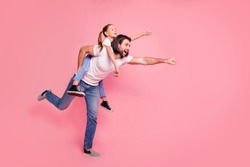 Full length side profile body size photo she her little lady he him his daddy dad hold little princess piggyback hands arms ready fly wear casual white t-shirts denim jeans isolated pink background