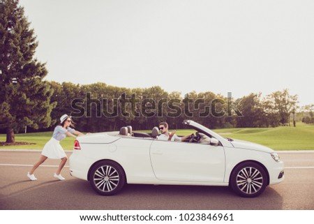 Full length side profile shot of gorgeous brunette lady in cap and brunet guy driver, both well dressed, in black trendy eyewear, resolving the car problem, park with green trees around, sunshine