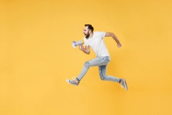 Full length side profile view image of crazy fun young bearded man 20s in white basic white t-shirt high jumping like running, screaming in megaphone isolated on yellow background, studio portrait.