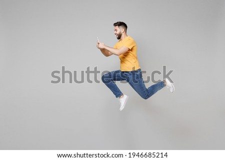 Full length side profile view of young bearded cool student man 20s in yellow t-shirt jump high hold mobile cell phone chatting using fast internet run isolated on grey background studio portrait.
