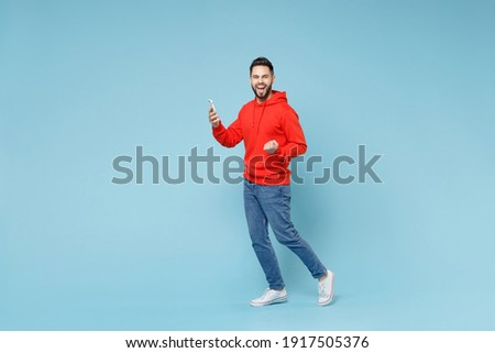 Full length side profile view of young caucasian happy bearded man 20s in casual red orange hoodie hold mobile cell phone walk do winner gesture clench fist isolated on blue background studio portrait