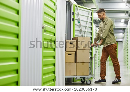 Full length side view at handsome bearded man loading cart with cardboard boxes into self storage unit, copy space