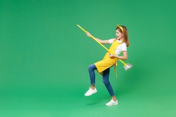 Full length side view laughing little kid girl housewife 12-13 in apron hold broom like play guitar while doing housework isolated on green background children studio portrait. Housekeeping concept